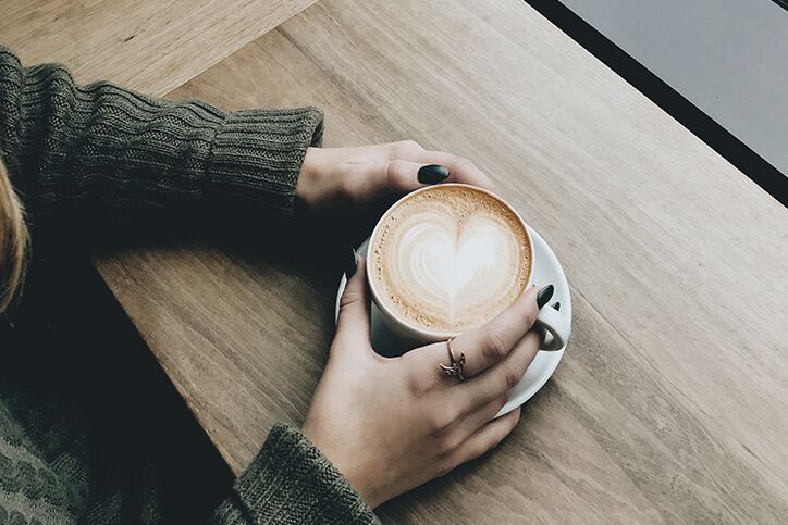 A woman with a cup of coffee with a cream heart in it