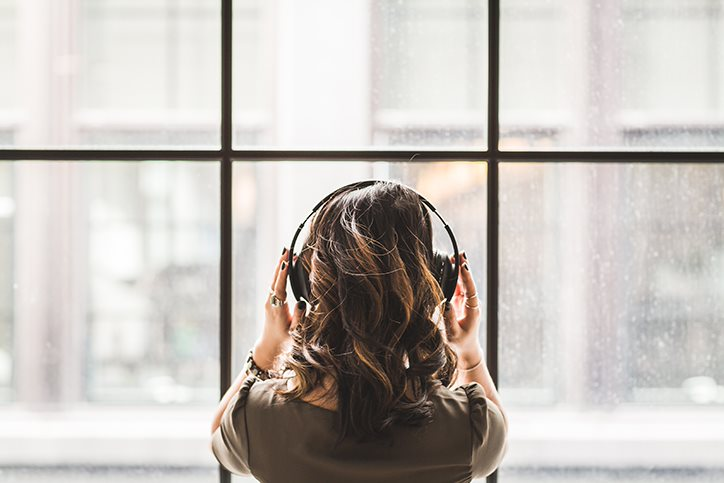 Woman looking outside while wearing headphones