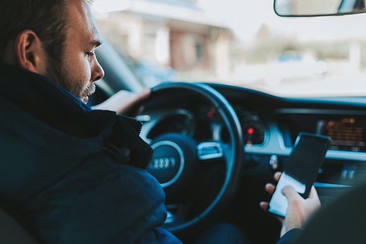 Man parked in a car outside a building looking at his phone