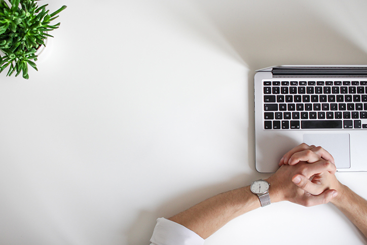 Top-view of hands at a laptop with a watch