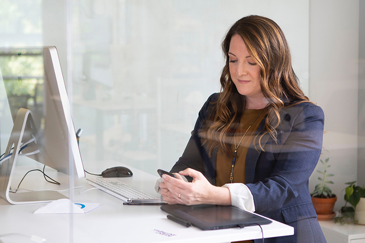 Woman standing at a desk looking at a smartphone