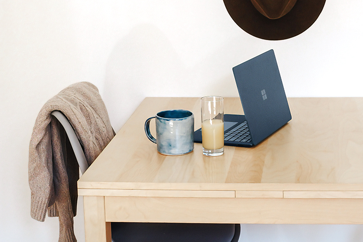 laptop on a desk with coffee and juice