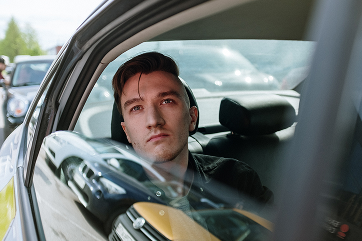 Man looking out of car from rear passenger seat