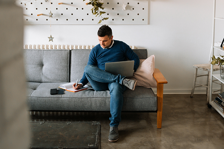 Man sitting on a couch at home with laptop and notebook