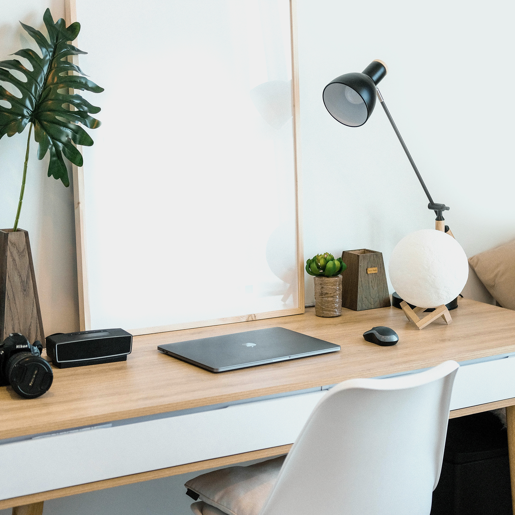 a desk with a laptop, lamp, and plant