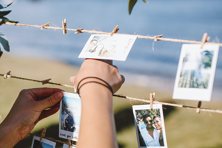 Hands hanging photographs on twine