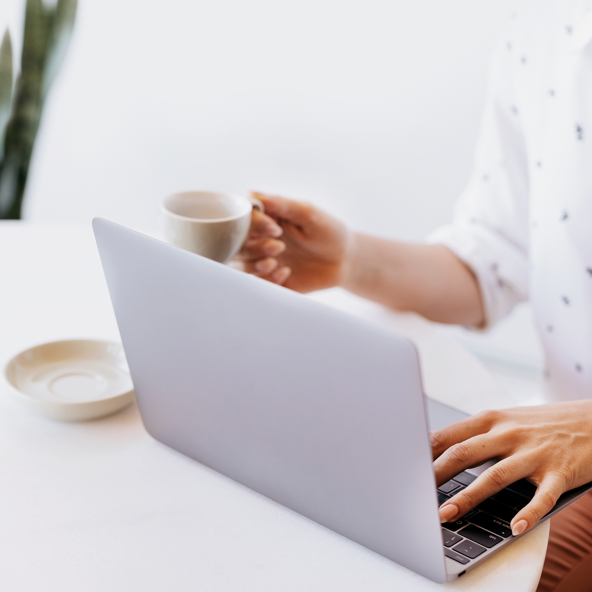 A person on their laptop and drinking coffee
