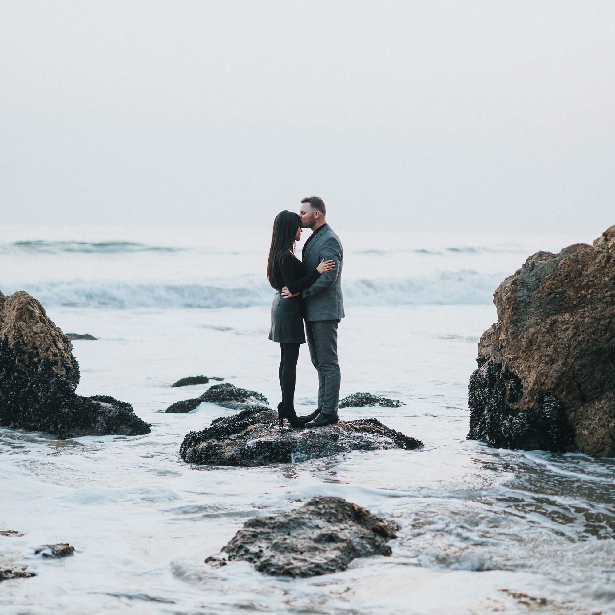 two people hugging by water